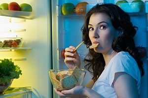 woman eating food in front of open fridge