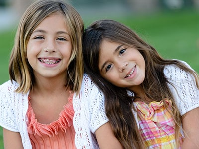 young girl in braces smiling with sister